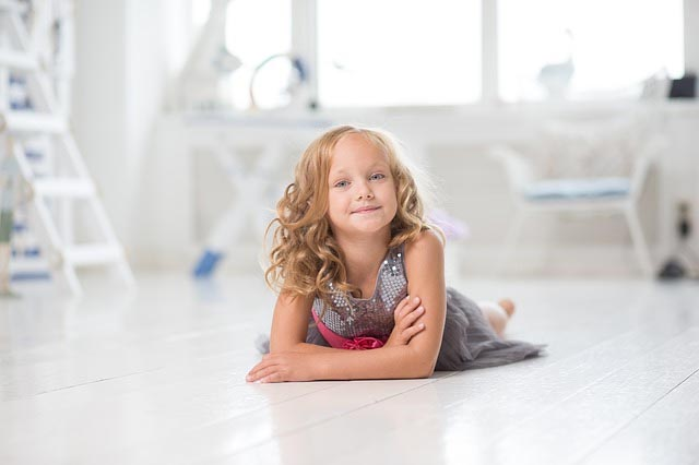 young girl lying on the floor smiling